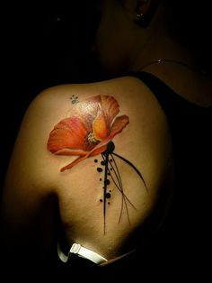 A piece of red poppy flower standing in the dark. It could have special meaning for the wearer.