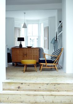 Modern London family home with pine floorboards, Ercol armchair and footstool, and gubi floor lamp in the music room