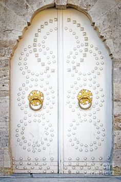 a pair of white Turkish doors ornamented with handmade round nails & brass handles { #istanbul }