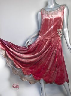 A showstopping dress from the 1920s fabricated from the most luxurious dusty rose colored silk velvet. A slightly tapered and therefore slightly more fitted bodice than is commonly found in this art deco art form, measuring 36 at the bust and 33 at the drop waist. A knockout skirt with scads of gathered silk velvet, beautifully ruched at the sides. Measuring 5 longer in the back, elegantly tapering from 42 in to 47 in the rear.  Lined with 12 inches of gold lame. Spectacular!