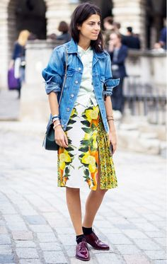 A denim jacket is layered over a vest and paired with a printed skirt, ankle socks and cranberry flats.