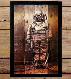 This handsome wood wall art is tattooed with the image of a deep sea diver, printed on reclaimed wood.