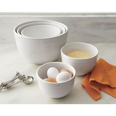 Deep nesting bowls with broad rims mix, serve and display in white high-fired earthenware.