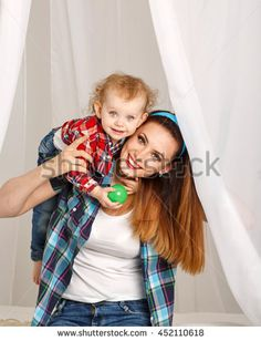 Mother and daughter at home. Young mother and baby daughter hugging and playing ball. Girls dressed in plaid shirt. Family Stock Photo, Mother And Baby, Hug, Photo Editing, Royalty Free Stock Photos, Girls Dresses, Daughter, Plaid, Couple Photos