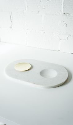 """Tom Dixon Stone Chopping Board;  A KITCHEN TOOL TO WORK ON AND SERVE FROM. CHOP, CUT AND ROLL ON THIS SLAB OF WHITE MORWAD MARBLE. SMALL MOVABLE BRASS DISC IS USEFUL FOR SERVING DRY FOODS. 16 1/2"""" BY 9 1/2"""". $125"""