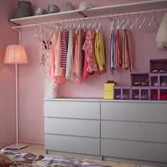 A bedroom with mirror, chest of drawers and clothes bars filled with clothes hangers