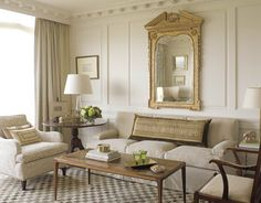 Howard painted the living room a warm, soft white, Farrow & Ball's Clunch. Howard turned an antique French tapestry into one long rectangular pillow because she prefers the massiveness of the shape to that of many small throw pillows. The room's showpiece is a George III gilded mirror with a broken pediment. Curtains in Schumacher cotton sateen are tucked directly under the cornice. An English mahogany breakfast table serves as an oversize side table.