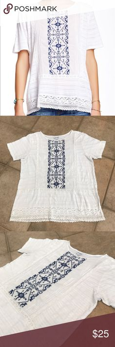 """Lucky Brand Panel Embroidered Shirt with Lace This shirt is preloved, size Medium, and made of 58% cotton 42% viscose. The top is super soft and features a crew neckline, short sleeves, embroidery on the front and an intricate lace trim. Shirt has a small hole on the back of the shirt and a small pull in the front, both shown in pictures above. The bust (pit to pit) measures about 20"""" flat across and length (shoulder to hem) about 25"""". All measurements are taken while the garment is laying…"""