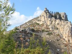 """Castello di Sant'Ilario - Kyrenia """"Sotto le rocce aguzze dai riflessi argentei e i pini rachitici dagli aghi verdi, la montagna scendeva a picco per mille metri sulla pianura costiera, sterminata distesa rosso ruggine punteggiata di miriadi di alberi bassi con le loro ombre, oltre la quale, a un centinaio di chilometri di mare azzurro, si scorgeva il profilo dell'Asia Minore e dei monti del Tauro. Perfino gli assedi, allietati da un panorama simile, devono aver avuto la loro compensazione."""""""