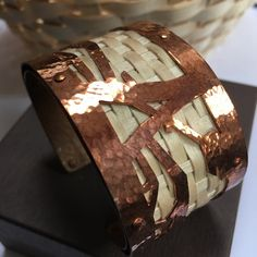Copper & Ash Cuff Woven ribbons of brown ash are set in hand cut and textured copper.  Based on ancient stories of the Wabanaki, the design represents the brown ash tree, split by the arrow of Gluskap.  From this split tree, the Wabanaki people appeared and use brown ash to this very day in their traditional basketry.  A blend of ancient craftsmanship and modern style.  Made in Maine by Native American designers!  A very special and unique piece to own.  This bracelet will receive lots of…