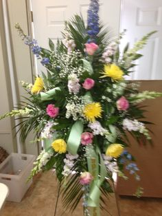 Fresh Funeral spray using blue Delphinus, white snapdragons, white stock, white monte casino, yellow Fuji mums, pink roses and baby's breath as filler. Pale green ribbon. March 2016