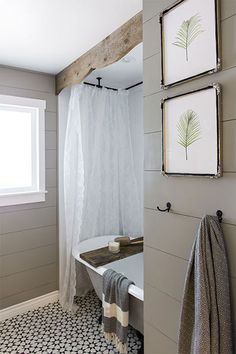 A valance made from old barnwood frames the shower curtain and hangs off the ceiling over the white cast-iron tub