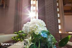 modern white wedding, beautiful white floral arrangement, sunlight shining through church window.