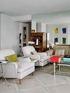 Muebles en blanco sobre los que destacan algunos detalles de color, como los cojines o los grabados de la pared