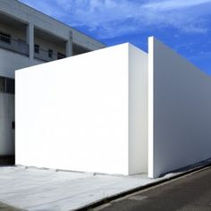 A narrow vertical slice at one corner is the only interruption to the monolithic facade of this plain white house in Miyazaki, Japan, by Hiroshima studio Tsukano Architect Office (+ slideshow).