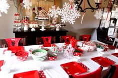 Table set for decorating Gingerbread Houses - Aprons on Chairs - Candies - White Snowflakes hanging overhead!