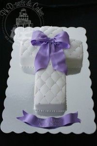 A cross-shaped baptism cake adorned with an edible purple bow. www.phdserts.com