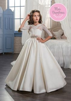 The Lexington flower girl dress is a lovely chic dress for special occasion. The top with 3/4 length lace sleeves, a tie-back waist, lace-up back with a keyhole cut, and a row of buttons, running down the long elegant pleated satin skirt, accentuate the vintage-inspired look. A rhinestones brooch detail at waist adorns the front. A perfect ball gown for young girls.