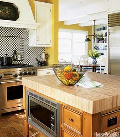 The island in a Chicago kitchen designed by Mick de Guilio is topped with durable end-grain bamboo, which is not only resistant to scratches and moisture, but is a quickly renewable natural resource. The microwave is tucked unobtrusively into the kitchen island. ELLEN MCDERMOTT - HouseBeautiful.com