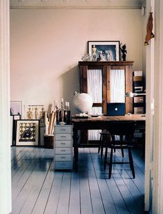 workspace / workplace / studio / office / wood / rustic / cabinet / desk / photographs / details / decor / globe