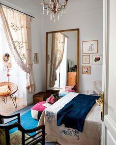 Decoração ousada, luz natural, quarto, tapete azul, espelho, cortina.