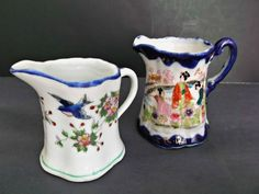 Two sweet vintage blue and white, flow blue, creamers. One measures three inches tall and shows two pretty bluebirds flying among pink, yellow flowers