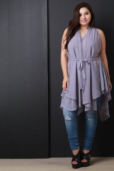 This semi-sheer plus size top features a v-neckline, sleeveless design, self-tie sash closure at waist, and asymmetrical sharkbite hemline. Accessories sold separately. 100% Polyester.