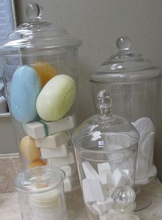 Squeaky-clean, glass apothecary jars are one way to categorize and display soaps, cotton pads, makeup wedges, Q-tips and other bathroom essentials.