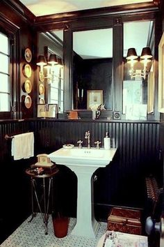 Nancy Keyes magnificent black bathroom in the manner of Mark D Sikes - love the sconces on the mirrors and the white pedestal sink
