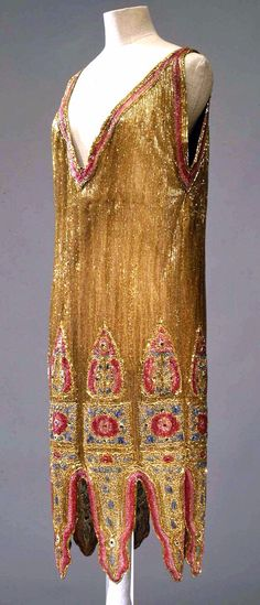 Evening dress, Italian manifacture, ca. 1925. Light brown slik tulle with deep V neckline, completely embroidered in gold coloured glass straws, strass in different colours and gold thread.