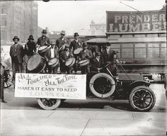 "An African-American drumming group perform on the back of a truck carrying a banner that reads ""All Together All The Time Makes It Easy To Keep St. Louis Clean"" on Market Street. Photograph, 1912. Missouri History Museum Photographs and Prints Collection. Swekosky-MHS Collection. n14688."
