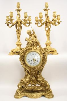 """This impressive example of an early 20th century French Rococo palace size clock set comes from the prestigious E. Colin & Cie of Paris foundry. The sculpted ensemble is detailed with crisp elaborate scrolling accented with a full figure cupid with quiver atop the clock. The clock & candelabras are decorated in a brilliant gold dore' finish. The set was commissioned by Tiffany & Co. & featured in the 1900 Paris Exposition. The clock has Roman numerals & bears """"Ti..."""