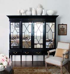 Elegant living room features a black armoire accented with mirrored doors atop sleek legs topped with a collection of white pottery alongside a bergere chair atop a gold Persian rug. Interior Design Inspiration, Decor Interior Design, Living Room Furniture, Home Furniture, Rustic Furniture, Living Room Designs, Living Spaces, Living Rooms, Elegant Living Room