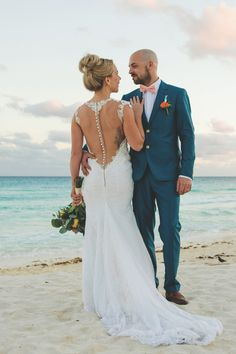 We love everything about Vickie and Daniel's wedding day looks for their destination wedding in Cancun, from her breathtaking backless gown to his bright pink bow tie! Photo credit: Cristina Gisselle Gonzalez Flores