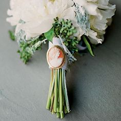 A bouquet of white peonies, seeded eucalyptus, and dusty miller is tied together with a cameo brooch belonging to the bride's grandmother.