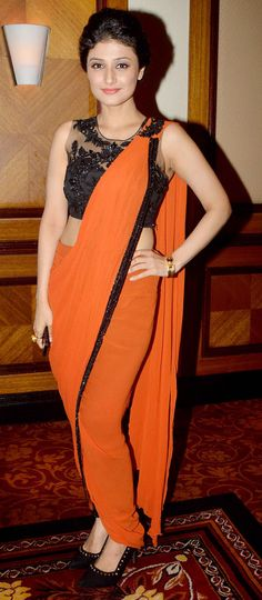 Raginni Khanna showed off her curves in a orange sari with a black blouse at the launch of Sony Pal TV channel.
