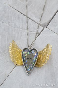 Love gives you wings! To make this necklace, we glued a fit-to-size stamped blank inside a heart bezel, filled it with dimensional gloss and glitter, and added filigree wings for a flutter effect.
