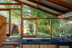 Cozinha com pia com tampo preto, janelas de vidro com caixilho de madeira, piso cinza escuro. Casa de Campo na Serra por Gabriela Baraúna + Denis Joelsons