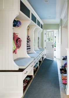 A great example of a functional mudroom. Individual compartments and chalkboard insets for each child. Bench seating and a combination of open and closed storage solutions do the trick. Multiple hooks per section to hang hats & coats at the same time. Wooden trays roll out for easy access. Lockers (not shown) also conquer the clutter.
