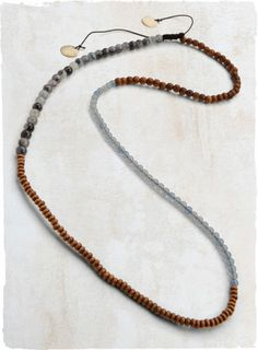 Strung with wood and marbled blue resin beads, the multi-wrap bracelet doubles as a striking necklace.