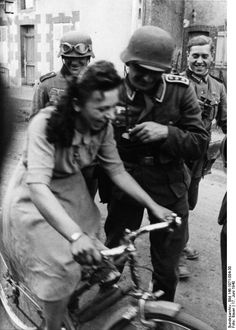 17/06/1940: at some point in occupied France, German soldiers help a woman to ride a bike. # 2GM #WWII