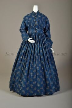 "Indigo dyed cotton w/ yellow printed leaf & stem pattern & white resist leaf veins; mandarin collar, bodice gathered from F & B yoke to wide waistband, CF opening w/ hand buttonholes, side pan- els, L shaped sleeves, very full gathered ankle length skirt; bodiced lined in natural linen; CB 55.5"" Date	1867-1869, ca."