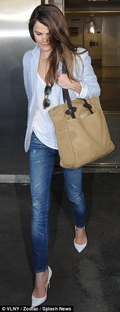 Traveling light: Keri Russell accentuates her slim shape in a white blouse, grey blazer, and skinny jeans.