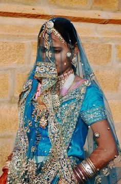 Hennaed hands, diaphanous veil, richly embellished sari, tons of bangles, exquisite jewelry - everything we'd expect from a Rajasthani woman.