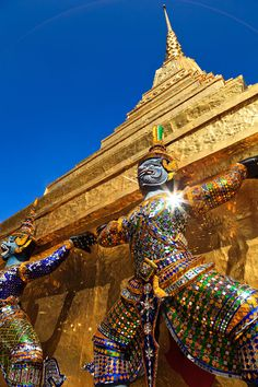 Guardian statues supporting the base of a golden Chedi outside the Royal Pantheon, known locally as Prasat Phra Dhepbidorn,Thailand