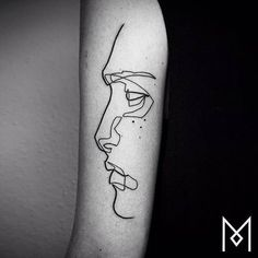 Continuous line face tattoo on the back of the left arm. Tattoo artist: Mo Ganji