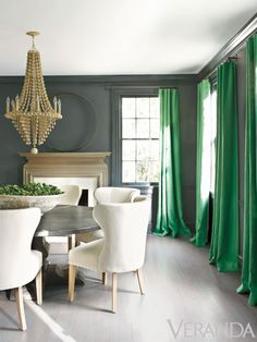 I love those green draperies---such a dynamic pop of color!  I also love the chandelier's color and those gray walls! Are you a fan of this socialite styled dining room? Find out what's your home decor personality by taking the Stylescope quiz at www.homegoods.com/stylescope