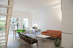 Minimal design interior with sofa, coffee table and Orange Slice Chairs in the back // styling by The Style Paper