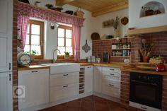 Prostorná rustikální kuchyně smoderními spotřebiči, doplněna památečnými kousky (formy, mlýnky, ošatky atd.) a cihlovým obkladem pro navození požadované…