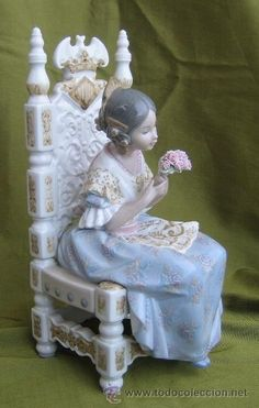Porcelain Lladró figurine, £300 - SOLD! Lladró porcelain figure of Valencian fallera seated on chair with pink roses. Cerca 1982. Hand Made in Spain on base of figure. Based on a 1979 Spanish film called: Visánteta Estáte Quieta. In mint condition. Fantastic piece. Measurements: 27,5cm max. height. Max width 13cm. Max. depth 12,5cm.
